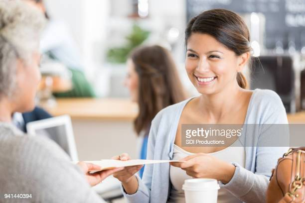 Businesswoman meets with client in coffee shop