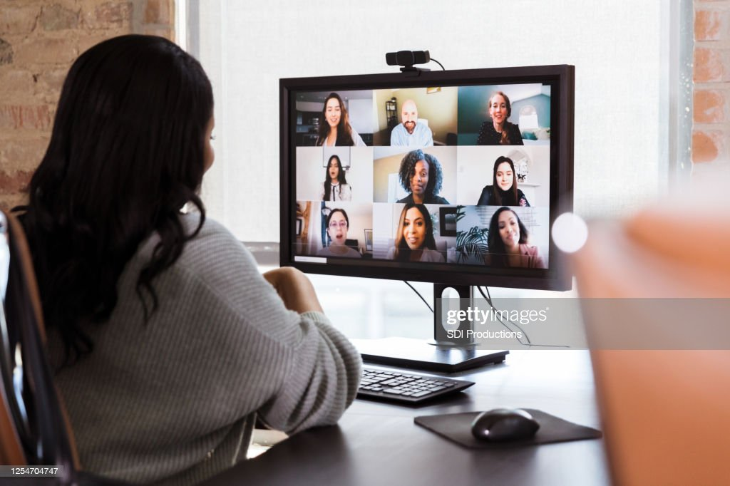 Businesswoman meets with colleagues during virtual staff meeting : Stock Photo