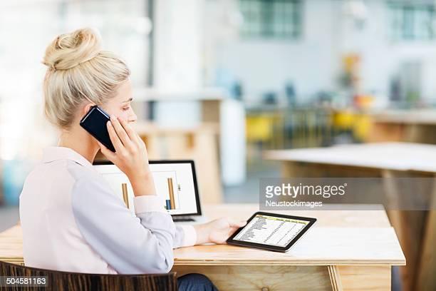 Empresaria multitareas-responder teléfono inteligente mientras usando tableta Digital