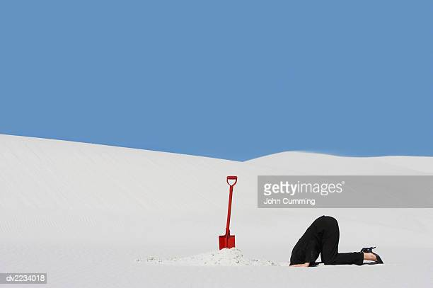 Businesswoman Next to a Spade Hiding Her Head in a Hole in Sand