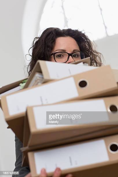 Businesswoman obscured by pile of folders