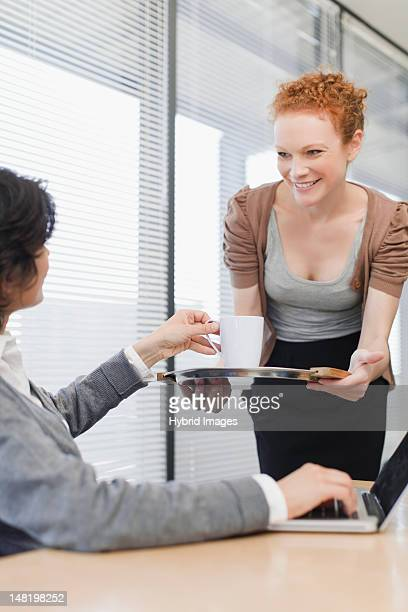 Businesswoman offering cup of coffee