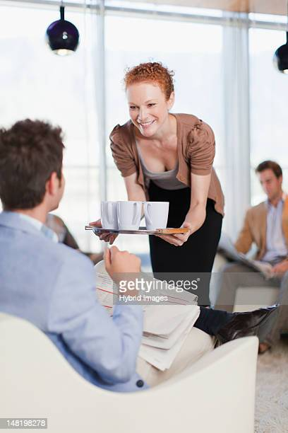 Businesswoman offering cups of coffee
