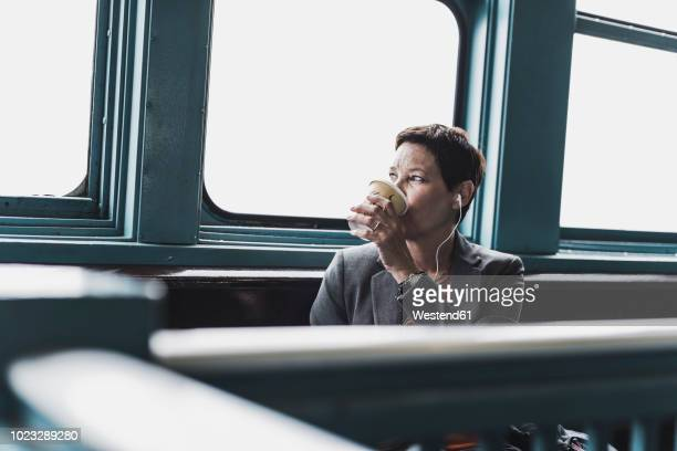 businesswoman on a ferry drinking coffee - fähre stock-fotos und bilder