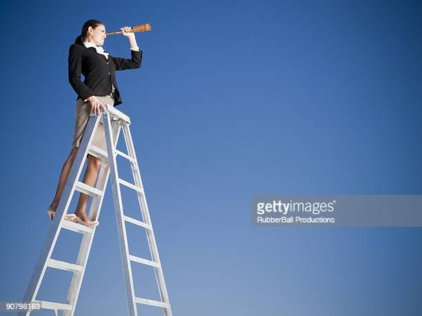 femme d'affaires sur une échelle avec un spyglass - longue vue photos et images de collection