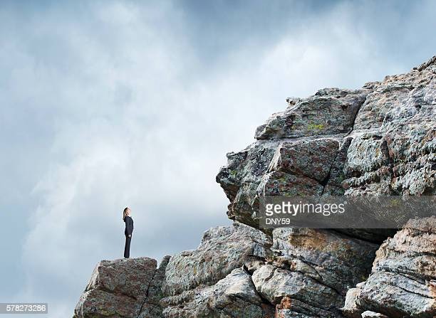 Businesswoman On A Rocky Slope Looks At The Challenges Ahead