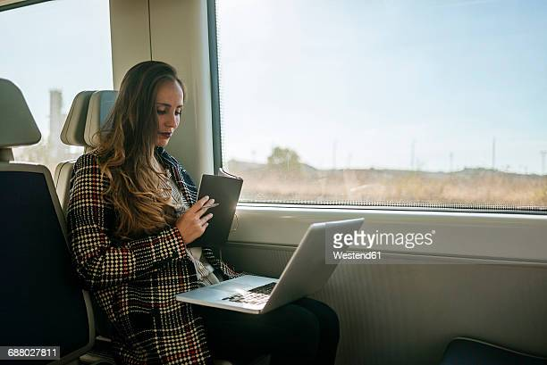 Businesswoman on a train with notebook and laptop