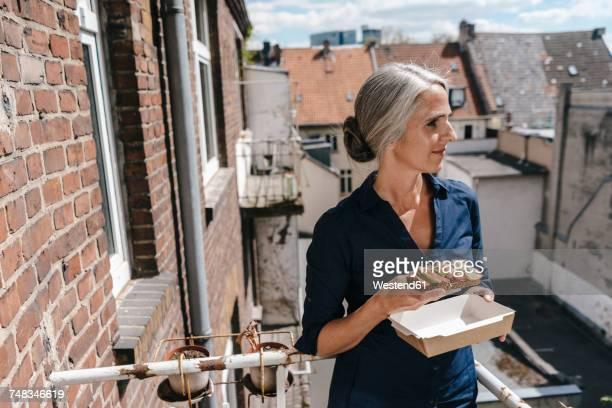 Businesswoman on balcony having lunch break