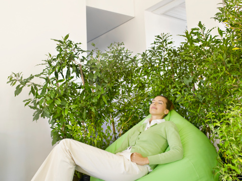 Businesswoman on beanbag surrounded by plants - gettyimageskorea