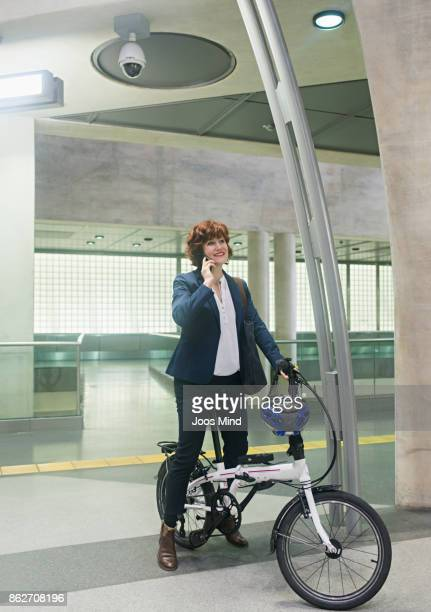 businesswoman on bike, having a phone call at subway sation