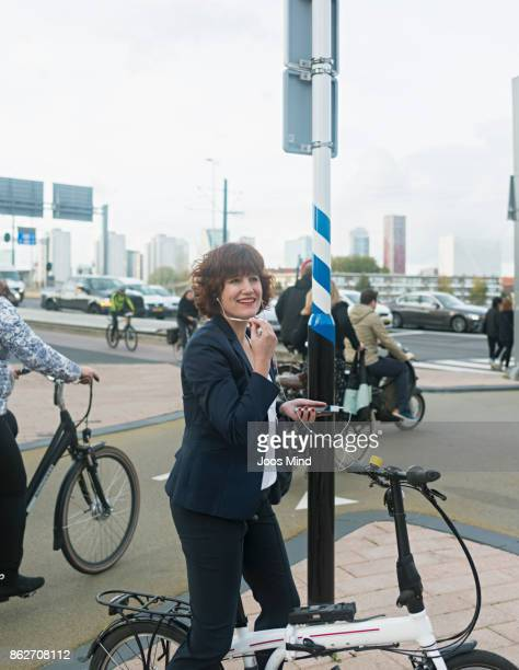 businesswoman on bike , having a phone call on crossroads