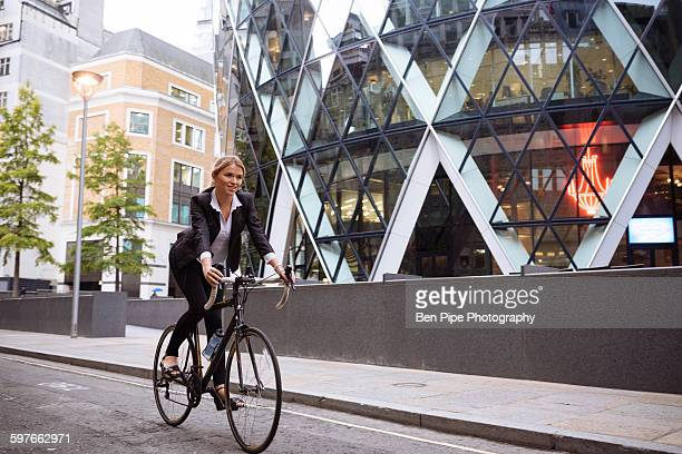 Businesswoman on bike passing 30 St Mary Axe, London, UK