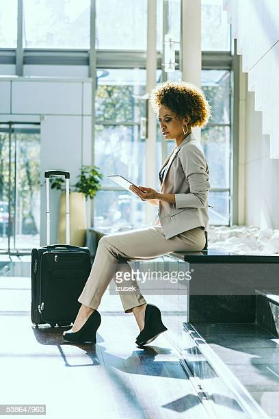 Businesswoman on business travel in hotel using tablet