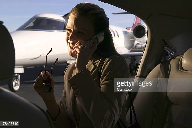 Businesswoman on cell phone in car near private jet