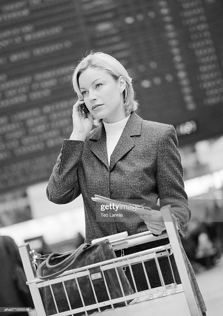 Businesswoman on cell phone with luggage caddy in front of arrival and departure board, b&w. : Stockfoto