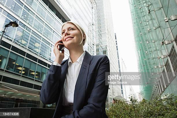 Businesswoman on cellphone amongst office buildings