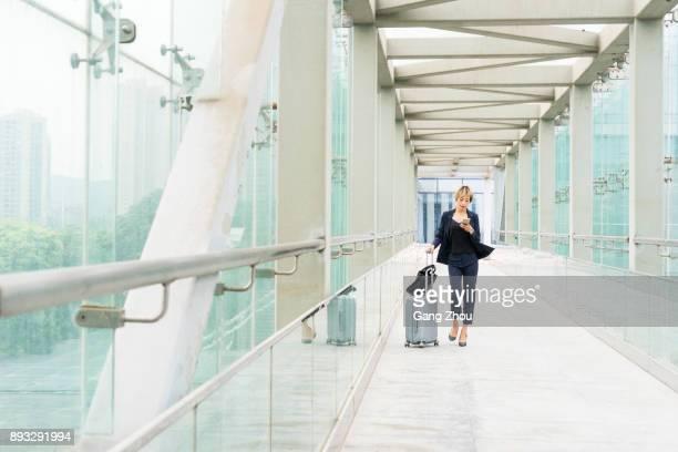 Geschäftsfrau auf Handy mit Koffer zu Fuß auf skywalk