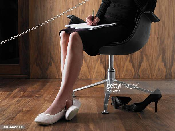 Businesswoman on chair, using telephone and making notes, low section