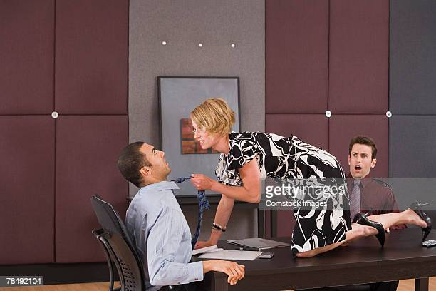 Businesswoman on desk harassing businessman