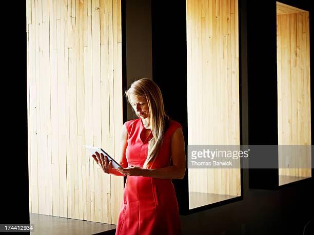 Businesswoman on digital tablet near office window