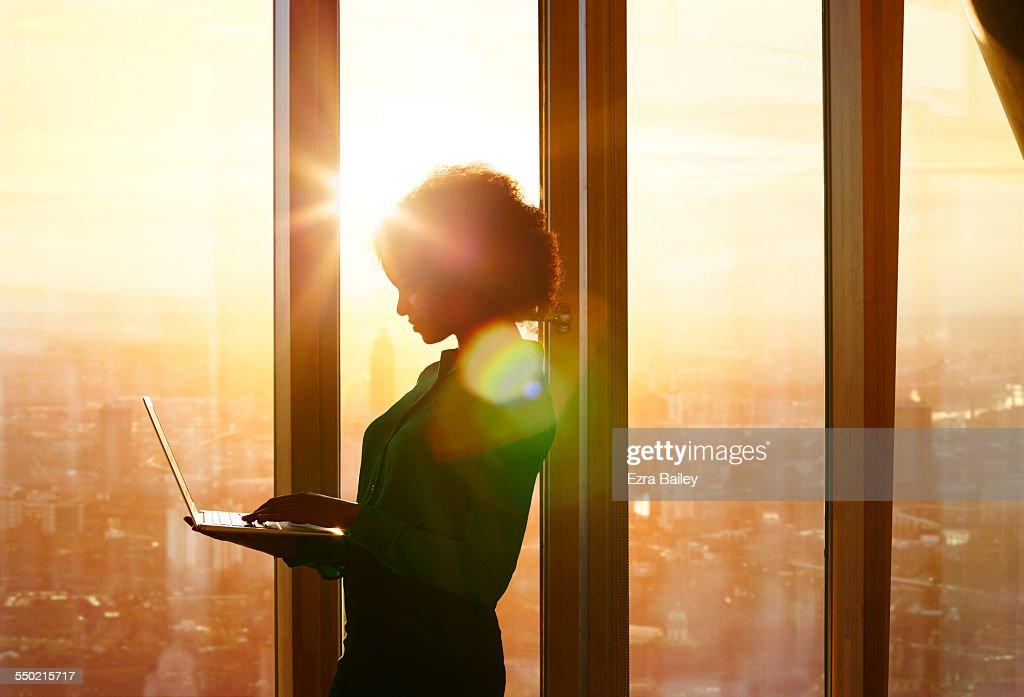 Businesswoman on laptop at window in morning sun : Stock Photo