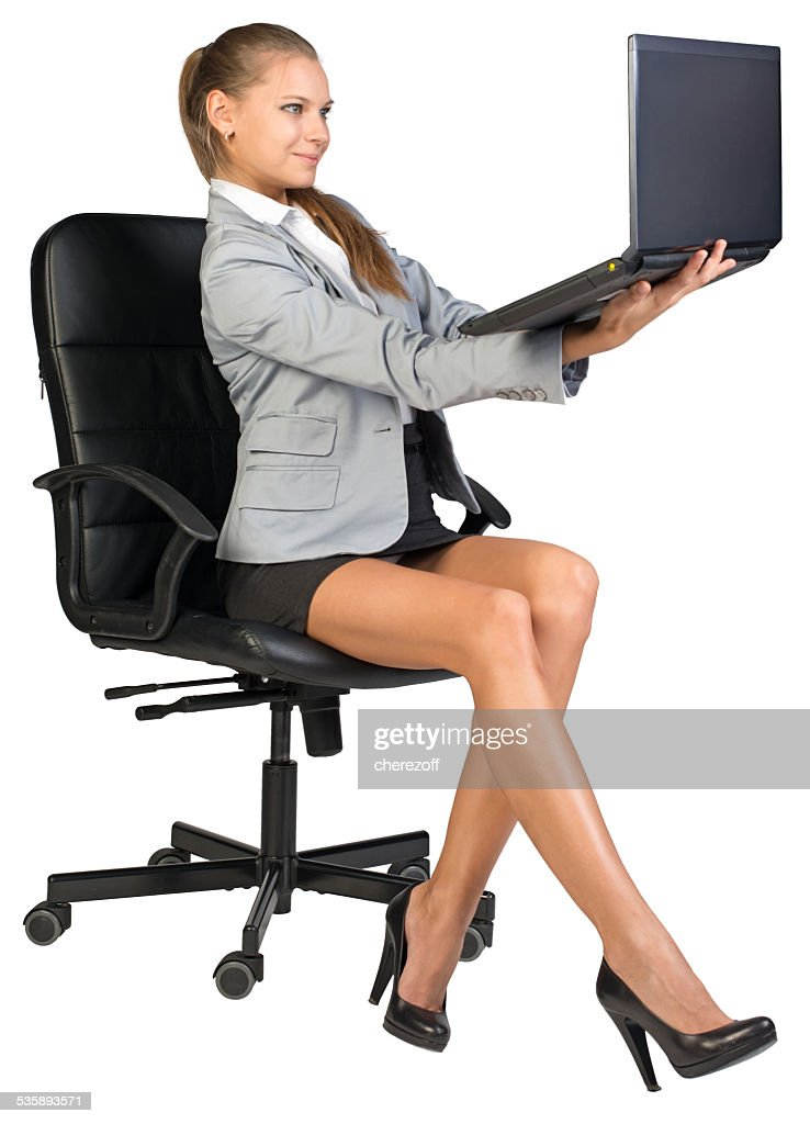 Businesswoman on office chair, holding laptop in her arms at : Stockfoto