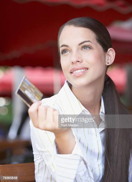 Femme d'affaires sur un patio extérieur en tenant la carte de crédit