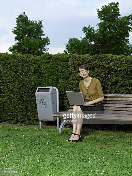 businesswoman on park bench with laptop