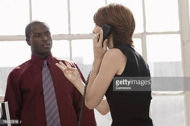 Businesswoman on phone gesturing to colleague