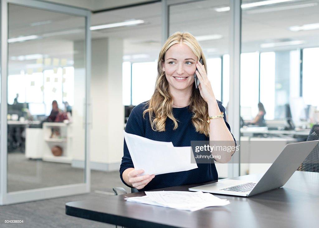 Geschäftsfrau mit Telefon in einem modernen Büro, Lächeln : Stock-Foto