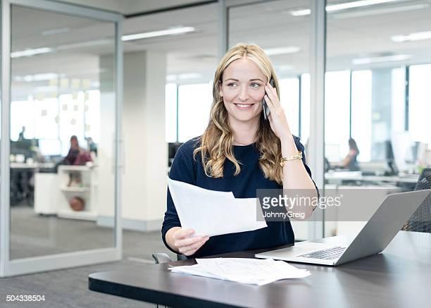 Geschäftsfrau mit Telefon in einem modernen Büro, Lächeln