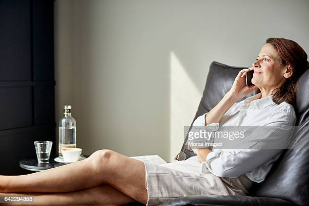 Businesswoman on phone relaxing in hotel room