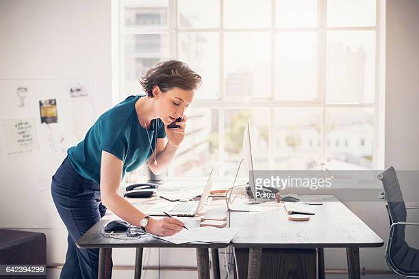 businesswoman on phone talking to client - brightly lit stock pictures, royalty-free photos & images