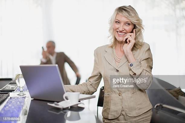 Femme d'affaires sur le téléphone à l'aide d'un ordinateur portable
