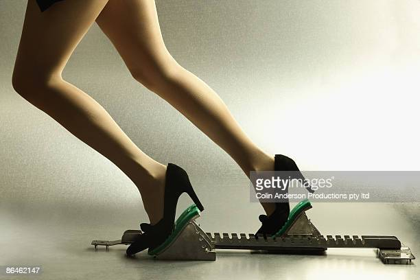 businesswoman on racing block - talons hauts photos et images de collection