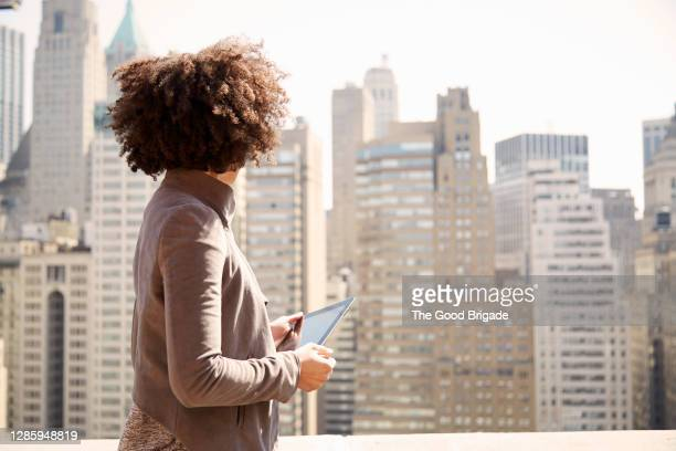 businesswoman on rooftop holding a tablet computer - rear view stock pictures, royalty-free photos & images