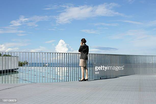 Businesswoman on smart phone in roof top
