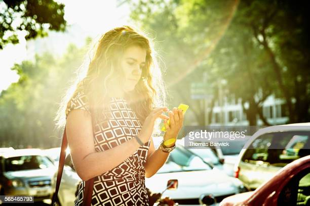 Businesswoman on smartphone while waiting for taxi