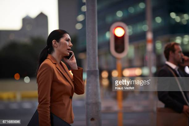 Businesswoman on street talking on the phone, at night