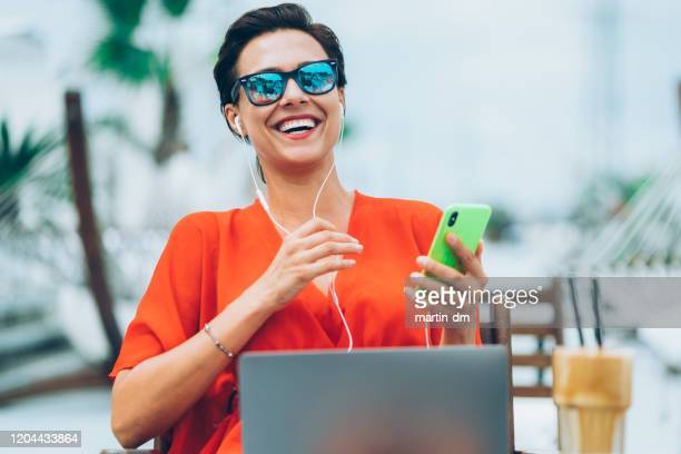 businesswoman on summer vacation talking on video call - nomadic people stock pictures, royalty-free photos & images