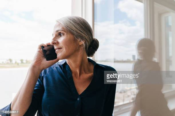 Businesswoman on the phone at the window