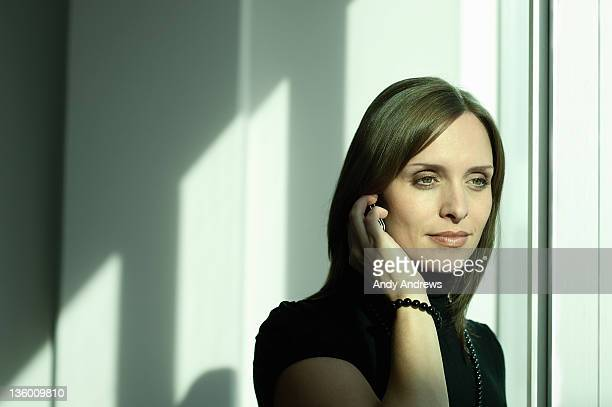 Businesswoman on the phone by window