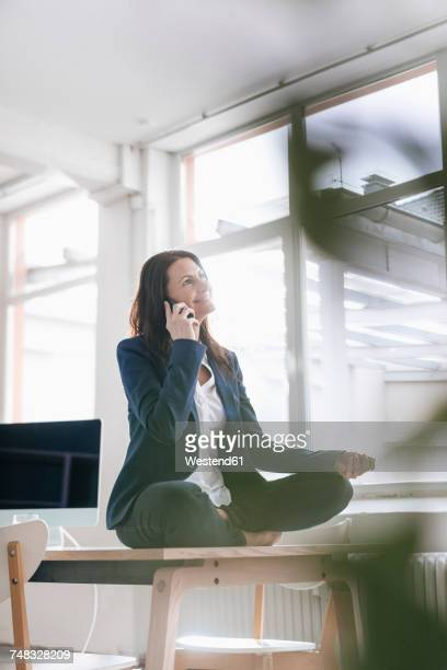 Businesswoman on the phone doing yoga exercise on desk in a loft
