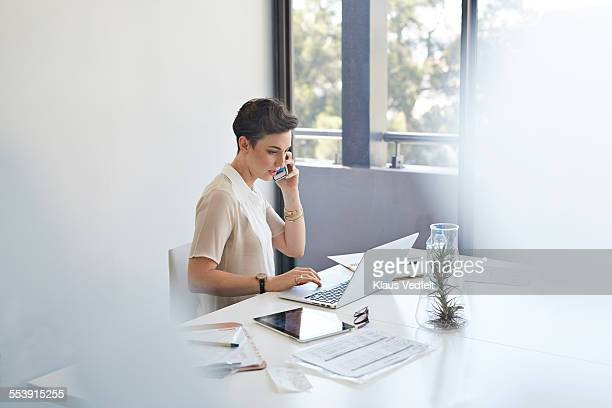Businesswoman on the phone & in front of laptop