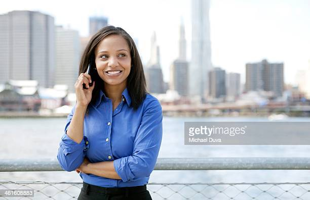 Businesswoman on the phone outside in Brooklyn overlooking Manhattan skyline