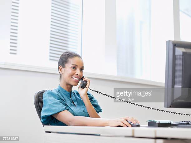 Businesswoman on the telephone at a computer in an office