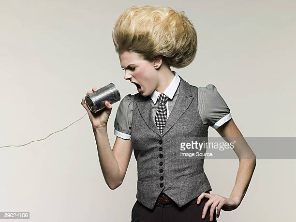 businesswoman on tin can phone - beehive hair stock photos and pictures