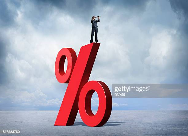 Businesswoman On Top Of Interest Rate Symbol Looking Through Spyglass