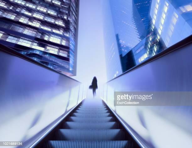 businesswoman on top of moving escalator at illuminated business district - al centro foto e immagini stock