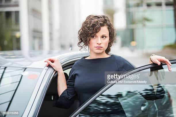 Businesswoman opening car door